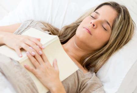 Beautiful woman falling asleep while reading a book photo