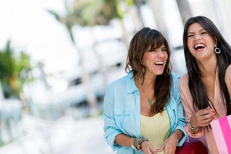 friends laughing: Happy shopping women having fun and laughing