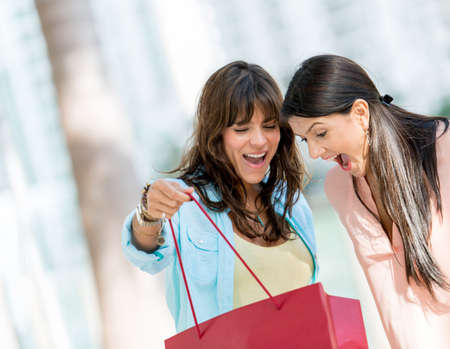 Excited shopping women looking in a bag Stock Photo - 19151041