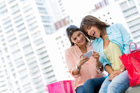 Happy shopping women looking something on a cell phone Stock Photo - 19151058