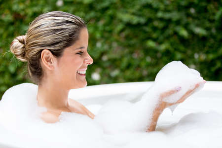 Woman taking a bubble bath in the hot tub photo