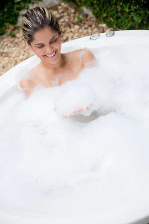 Happy woman taking a bath in a hot tub Stock Photo - 19151048