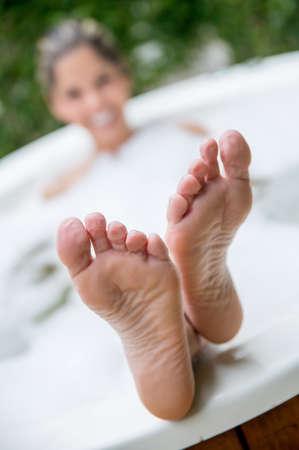 ногами: Женщина, расслабиться в джакузи, принимая ванну Фото со стока