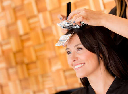Woman coloring her hair at the beauty salon photo