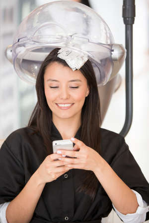 Woman at the hairdresser texting on her cell phone photo