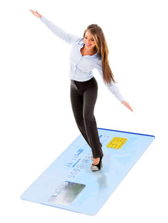 Business woman flying on credit card as a magic carpet - isolated photo