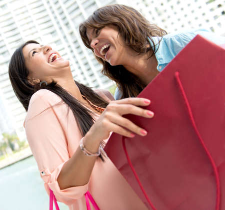 Excited shopping women looking at their purchases photo