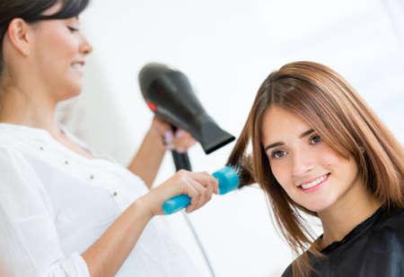 stilist: Saçları kurutma kuaför darbede güzel kadın