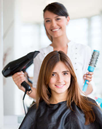 straighten: Happy woman at the beauty salon getting a hair cut