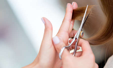 Cutting the split ends of damage hair at the beauty salon photo