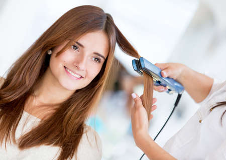 Stylist using a hair straightener on a woman at the salon photo