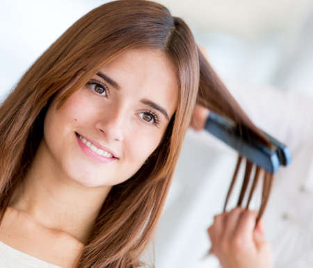 Woman straightening her hair at the beauty salon photo