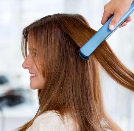 peluquerias: Mujer en el sal�n de belleza que se endereza el pelo Foto de archivo