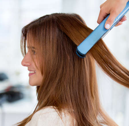 Woman at the beauty salon straightening her hair photo