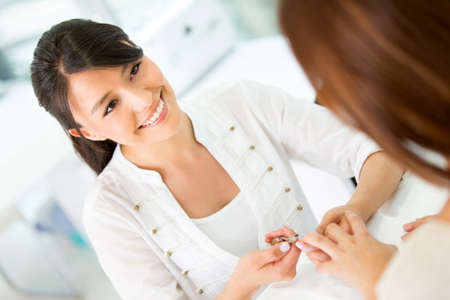 Friendly manicurist working at the beauty salon and smiling photo