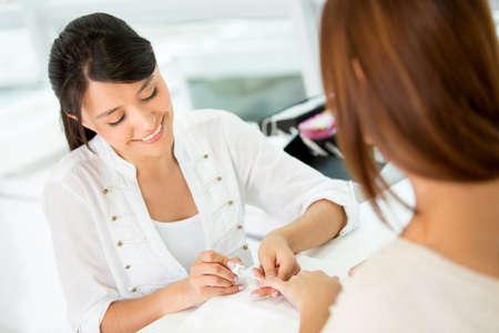 estilista: Mujer que hace la manicura y la aplicaci�n de esmalte de u�as Foto de archivo