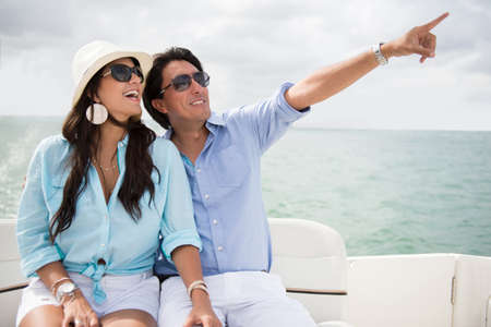 Happy couple in a yacht enjoying the summer and pointing photo