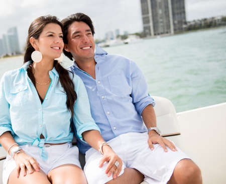 Romantic summer couple in a boat looking very happy photo