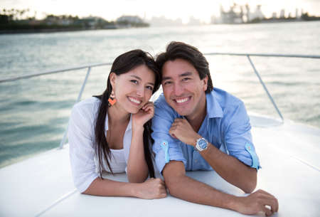 Happy couple in a yacht enjoying sailing and smiling photo