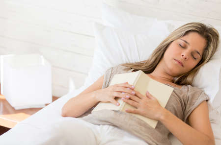 Tired woman reading a book and falling asleep photo
