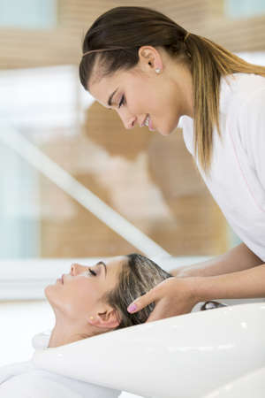 Woman at the beauty salon washing a clients hair photo