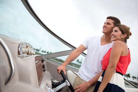 Romantic couple driving a boat and looking happy photo