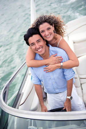 Beautiful couple hugging on a yacht looking happy photo