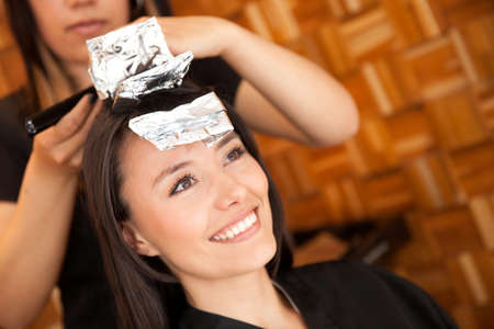 feminine beauty: Woman dying her hair at the beauty salon Stock Photo