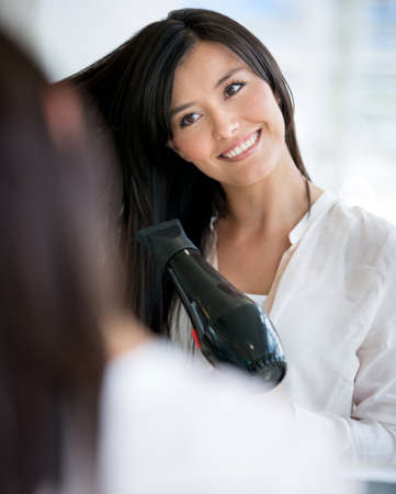 Woman at the hair salon blow drying her hair photo