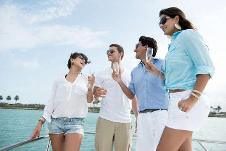 male friends: Group of friends on a boat having fun and drinking champagne Stock Photo