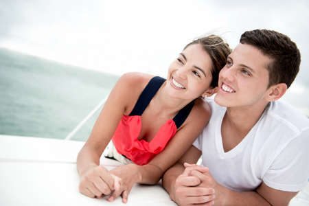 Loving couple sailing on a boat looking very happy photo