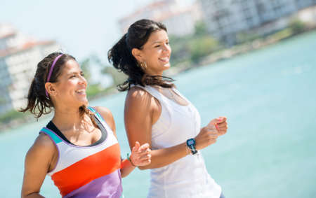 run out: Happy women running outdoors by the beach - fitness concepts