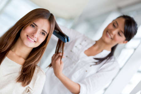 straightener: Stylist straightening hair of a client at the beauty salon Stock Photo