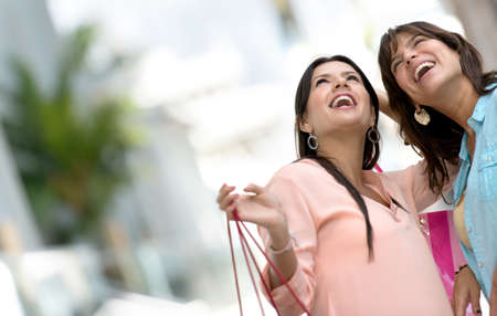 Happy shopping women having fun and holding bags photo