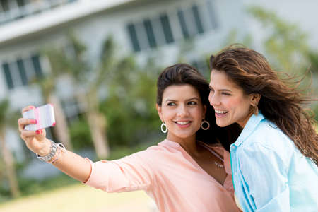 Women taking a picture of themselves with the mobile phone photo