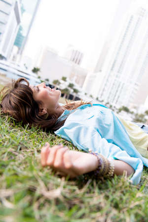 Pensive woman lying on the grass at the park and looking up Stock Photo - 19226765