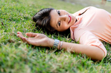 Portrait of a beautiful woman lying outdoors and smiling Stock Photo - 19226763