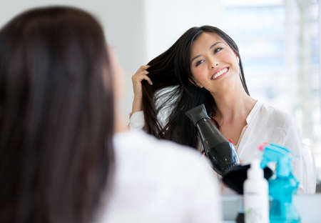 Beautiful woman blow drying her hair at the salon photo