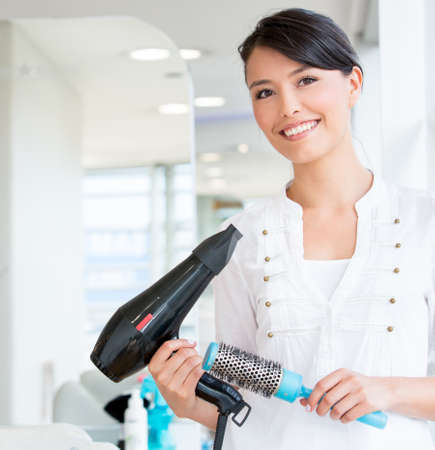 Female stylist at the beauty salon looking very happy photo