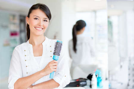 Beautiful woman at the beauty salon holding a hair brush photo