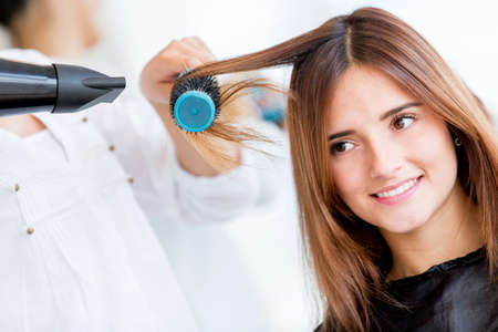 stylists: Woman portrait blow drying her hair at the beauty salon Stock Photo