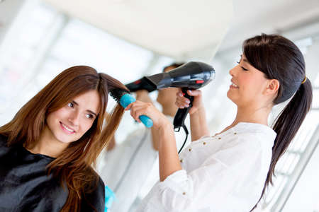 Stylist blow drying hair of a client at the beauty salon photo