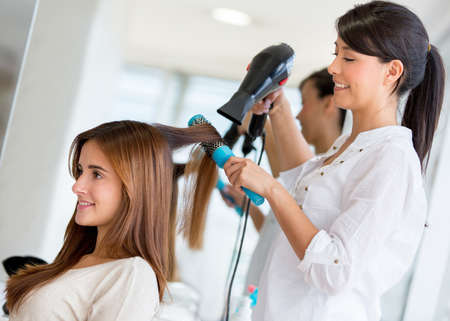 Stylist drying hair of a female client at the beauty salon photo