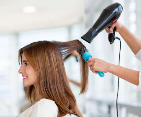 Beautiful woman at the hairdresser blow drying her hair photo