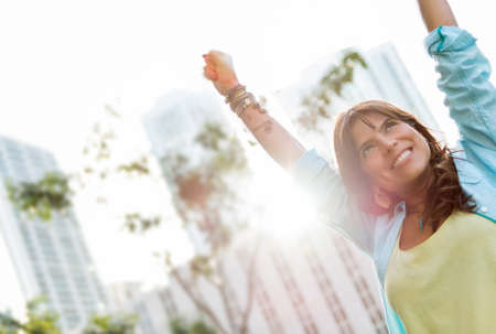 Successful woman with arms up outdoors celebrating photo