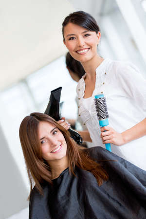 Woman at the hairdresser blow drying her hair photo