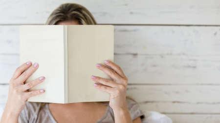 mujer leyendo libro: Mujer que lee un libro y que cubre su cara Foto de archivo