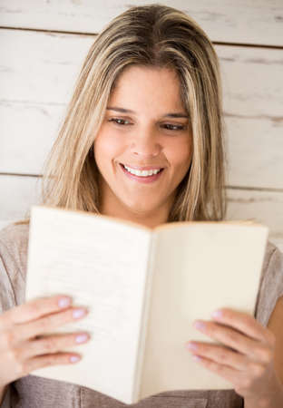 Beautiful woman reading a book and smiling Stock Photo - 19317407
