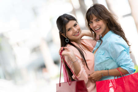 Happy female shoppers with shopping bags smiling photo