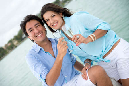 Couple drinking champagne on a yacht looking happy photo